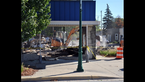 THE FACADE is all that remains of the former doctor's office and apartments at the corner of Kaiser and Third streets in Pinconning on Monday morning. Walt's Trucking & Excavating of Pinconnng began demolition of the partially collapsed structure last Thursday. --Journal Photo