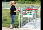 TINA BAUER, NBCF BOARD MEMBER, cuts the ribbon to officially open the new Pinconning Dog Park along the Pinconning Nature Trail. Over 50 people attended last Wednesday's event.              --Journal Photo